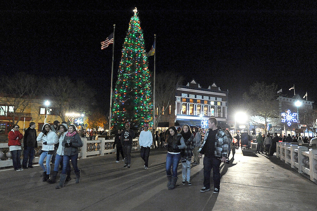 Description of . People stroll across the School St. Bridge towards the Creekwalk as the Vacaville Christmas Tree glows on Tuesday, December 3, 2013 after the 31st Annual Merriment on Main Celebration concluded. Joel Rosenbaum/JRosenbaum@TheReporter.com