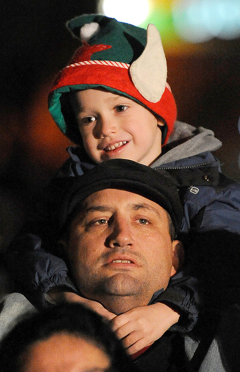 Description of . Wearing and novelity elf hat, Chase Newland, 6 of Vacaville sits on his dad, Chad Newland's shoulders as he wait for the lighting of the Vacaville Christmas Tree and the arrival of Santa Claus during the 31st annual Merriment on Main Celebration on Tuesday, December 3, 2013.  Joel Rosenbaum/JRosenbaum@TheReporter.com