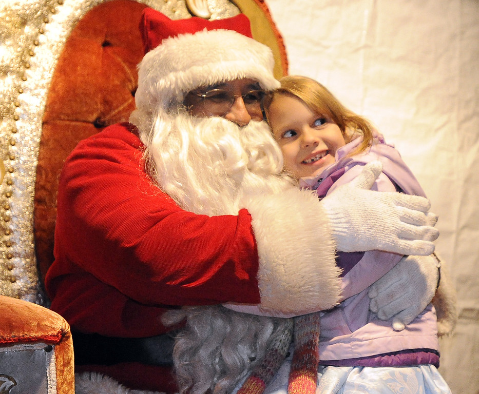 . Emily McCue, 6 of Vacaville gives Santa Claus a big hug after she told him her wish list. Santa hung around to listen to children\'s wishes after he flew in to help light the Christmas Tree during the 31st annual Merriment on Main on Tuesday, December 3, 2013. Joel Rosenbaum/JRosenbaum@TheReporter.com